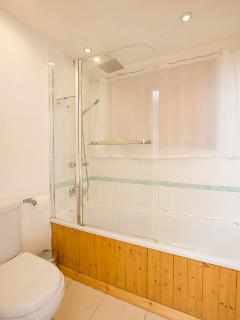 Tiled bathroom with shower over bath. Sink unit has storage for toiletries.  Heated towel rail.