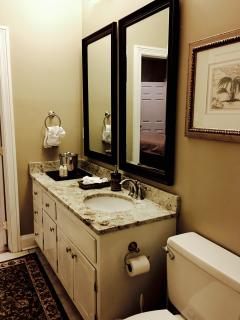 Dark mirror frames accent the chocolate specks in ivory granite counter top. Good taste abounds!
