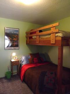Twin bunk bed with full bed below.