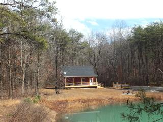The 'Red Barn' looks out over the fire pit, pond, and mountains