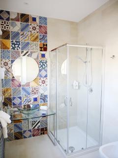 Wonderful ancient Sicilian majolica tiled bathroom has a big shower, wc and bidet.