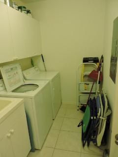 Laundry room with a washer & dryer along with beach chairs and laundry tub