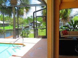 View of canal, pool and lanai with comfortable seating