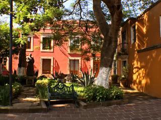 Fachada de la casa VH con frondosos árboles y bellos agaves