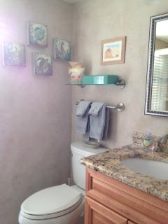 Remodeled master bath with new lighting, maple vanity, granite counter