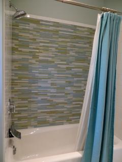 Tub area highlighted by sea glass tile, rainfall shower head, and water fall tub spout.