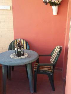 Terraza con mesa y sillas en la habitación principal a la calle.