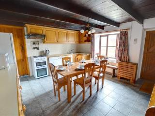 Good sized fitted kitchen with central dining table and beamed ceiling