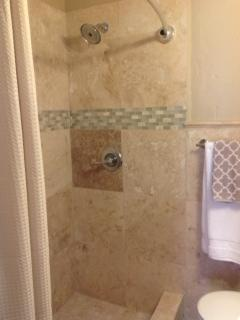 Master bathroom with shower, travertine tile