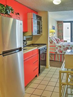 This quaint efficiency kitchen features a full-sized fridge and stove