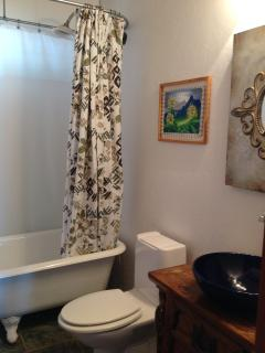 This bathroom has a soaker claw foot tub and vessel sink.