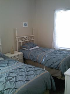 bedroom three has 2 twin beds and ceiling fan.