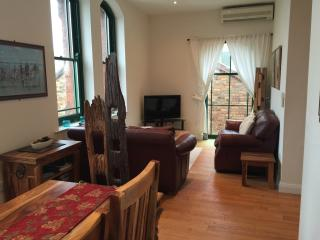 open plan living area with two leather 2 seater sofas and flat screen tv
