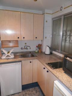 Kitchen with oven/grill, electric hob and microwave.