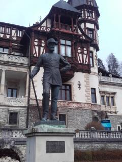 Statue of King Charles Compared to all tourists looking Peles Castle
