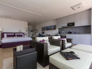 Wohnbereich mit Blick auf Bett, Garderobe, Schreibtisch und Küche.