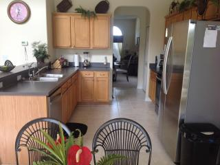 Well equipped kitchen adjacent to nook. Views of the pool deck and garden