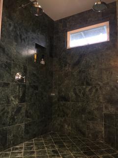 Upper master bath: walk-in stone shower with double rain showerheads.