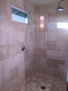 Lower Master King walk-in stone shower with natural light and rain showerhead.