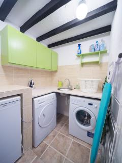 Utility room with washer, dryer, freezer, iron and ironing board.