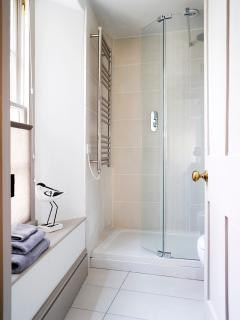 Underfloor heating in the bathroom with walk in shower, washbasin, toilet and heated towel rail.