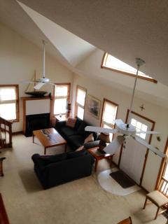 View from second floor hallway to open concept floor plan. Dining area abuts living area.