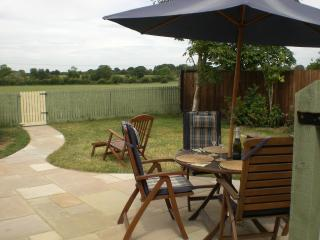 Enclosed garden with patio overlooking open countryside, garden furniture & charcoal BBQ.