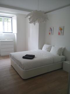 Large bedroom with double bed, large wardrobe and chest of drawers