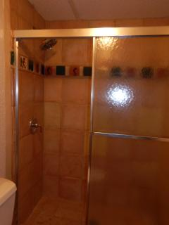 Shower has custom tile work.