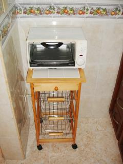 Mini toaster oven on stand in kitchen.