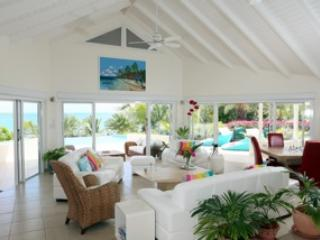 Large living room with inside dining overlooking pool and Nonsuch Bay