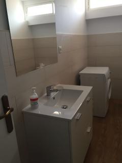 Cuarto de baño reformado en enero con lavadora.