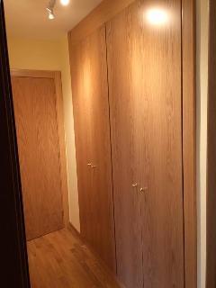 Vestidor de la habitación de matrimonio con dos armarios empotrados dobles con perchas.