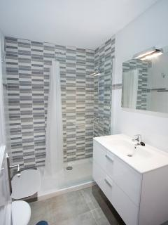 The bathroom with a shower, wc and washing machine.