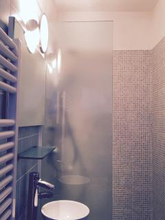 Shower in a luxurious mosaic tile bathroom with modern, designer fittings and lighting.
