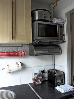 Small kitchen fully equipped with microwave, toaster, slow cooker
