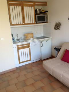 Kitchenette with ceramic hob, oven, washing machine, storage space and fridge