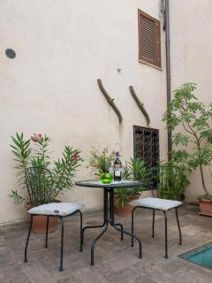 Table in the courtyard, inviting to read a book or to taste a good drop of local wine