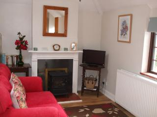 Pretty lounge of Fir Tree Cottage with glimpse of the sea over the garden and patio