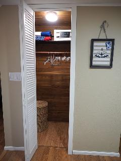 The cedar closet includes an iron & ironing board, as well as beach towels and laundry basket.
