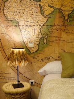 Apartamento NAIROBI. Detalle de mesilla, lámpara y mapamundi en la habitación doble de dos camas