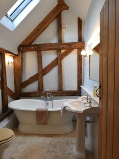 Bathroom with cast iron roll-top bath and shower.