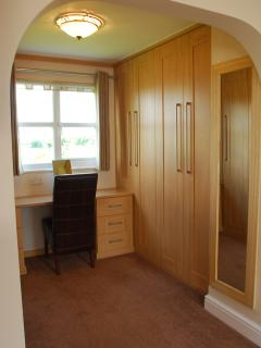 Ample wardrobe storage space with dressing area and desk area with seat overlooking farmland