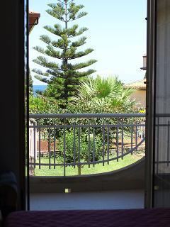 Camera da letto matrimoniale con balcone sul giardino e vista mare