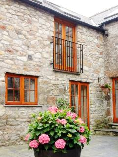 Juliet balcony  with bedroom below opening onto  the courtyard furnished with hydrangeas and shrubs