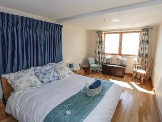 Master bedroom with queen size bed and direct sea views. The property has solid oak wood flooring.