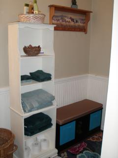 Corner of bath; bench and shelf storage, hooks, towels and toiletries