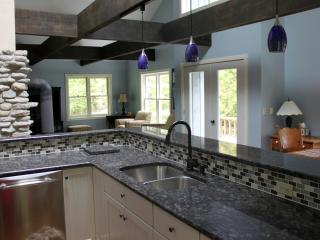 Granite countertop with stainless dishwasher.  Lots of light from windows and skylights.