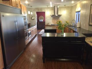 Kitchen with 2 islands, Viking gas range, double oven and side by side fridge/freezer.