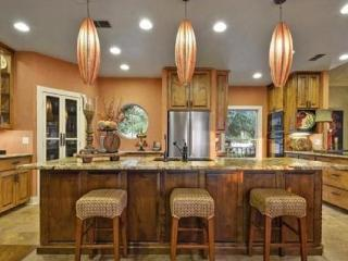 Fully stocked gourmet kitchen with two large islands with barstools